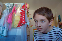 Young boy searching for a toy in his sister's bedroom.