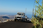 Jeeps on narrow mountain road overlooking the town of Arona the hills and sea, Arona,Tenerife, Canary Islands.