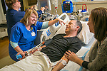 Sharon Norman, clinical research coordinator, talks with a brain tumor patient while he gets an infusion in Duke Clinic.