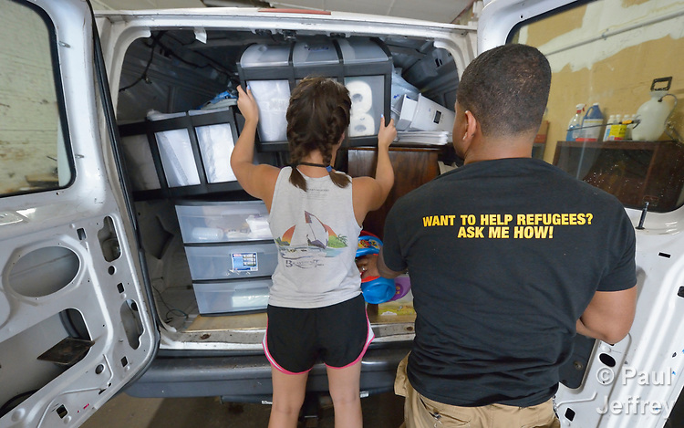 Church World Service staff load a truck with household goods in a warehouse in Lancaster, Pennsylvania. They are furnishing the apartment of a refugee family about to arrive in the United States.<br /> <br /> Photo by Paul Jeffrey for Church World Service.