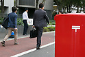 Pedestrians walk past a post mailbox in downtown Tokyo on October 29, 2015, Tokyo, Japan. The share price for Japan Post Holdings Co. public offering was set at 1,400 yen (11.58) for its debut on the Tokyo Stock Exchange next November 4. This price was at the high end of expectations and the government hopes that many Japanese citizens will take the opportunity to invest in the company. (Photo by Rodrigo Reyes Marin/AFLO)