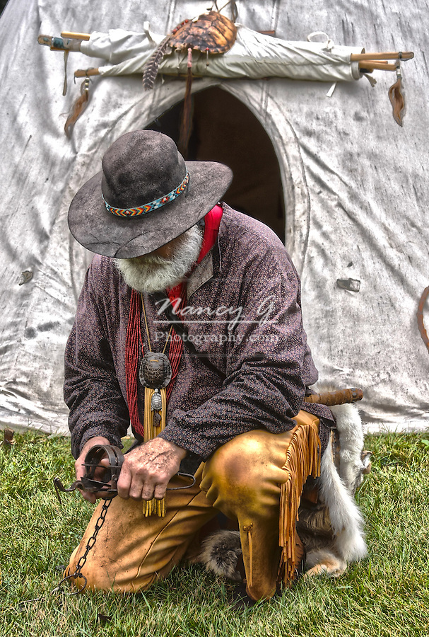 A mountainman trapper working with his trap by a tipi