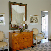 In the master bedroom two elegant armchairs flank a chest of drawers situated under a large mirror