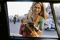 Indian woman begging while carrying her child, India