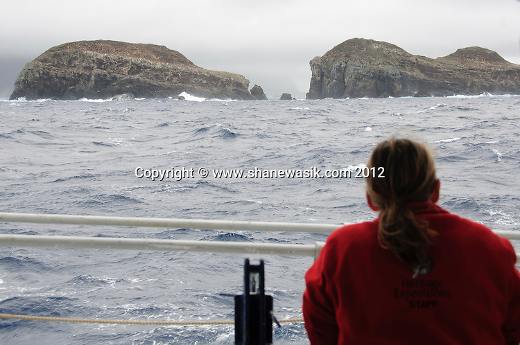 Expedition staff looking out at the Chanter Island, Kermdecs during stormy conditions.