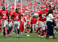 Ohio State football players avoid running over a Buckeye cheerleader following the Buckeyes' 76-0 win over Florida A&M in the NCAA football game at Ohio Stadium in Columbus on Sept. 21, 2013. (Adam Cairns / The Columbus Dispatch)