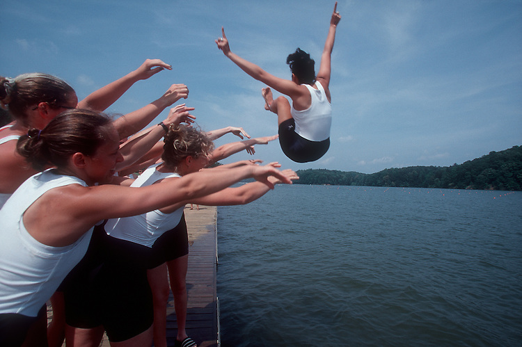 Women rowers celebrate by tossing the coxswain.
