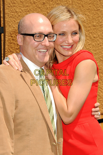 "MICKE MITCHELL & CAMERON DIAZ.Attending the ""Shrek Forever After"" Los Angeles Film Premiere held at the Gibson Amphitheatre, Universal City, California, USA, 16th May 2010..arrivals half length red dress glasses arm around beige brown suit green tie white shirt smiling hug hugging .CAP/ADM/BP.©Byron Purvis/AdMedia/Capital Pictures."