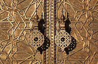 Golden doors and handles, Royal Palace, 17th century, Fes, Fes-Boulemane, Northern Morocco.  The Royal Palace compound in Fes-el-Jedid covers 80 hectares and contains gardens, mosques and a 14th century madrasa or religious school. As a residence of the king of Morocco it is closed to the public. Fes-el-Jedid was founded in 1244 as a new capital by the Merenid dynasty, and contains the Mellah, or Jewish quarter. Picture by Manuel Cohen