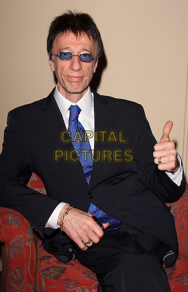"ROBIN GIBB.""An Audience with Robin Gibb"" a Lunch and Q&A Session in aid of the Heritage Foundation at the Grosvenor House Hotel, Park Lane, London, England, January 18th 2009..half length suit sitting thumb up tinted glasses blue tie glasses .CAP/ROS.©Steve Ross/Capital Pictures"