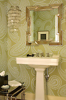 The exaggerated paisley wallpaper makes a dramatic statement in this small bathroom