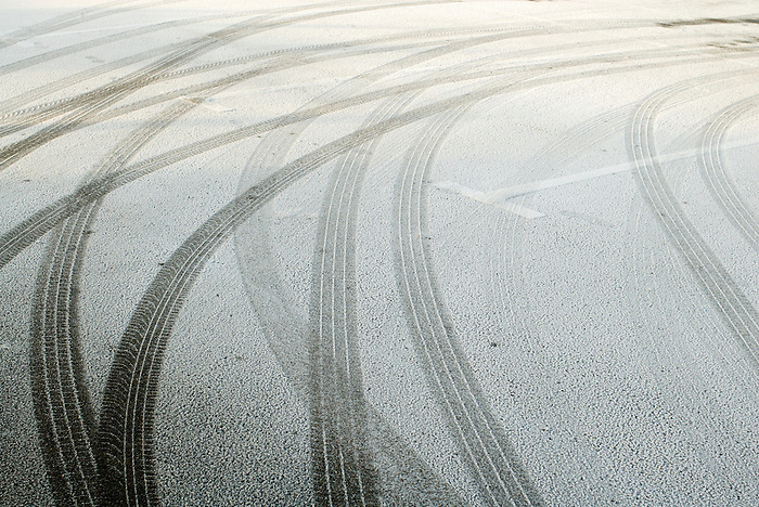 Tyre tracks and footprints in an icy parking lot.