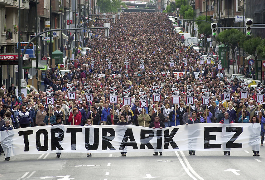 "Thousands of people attend a demonstration against torture on June 8, 2002, in Bilbao, Basque Country. The main banner reads in Basque language ""Torture no"" and the little banners read ""6.000 people tortured"". (Ander Gillenea / Bostok Photo)"