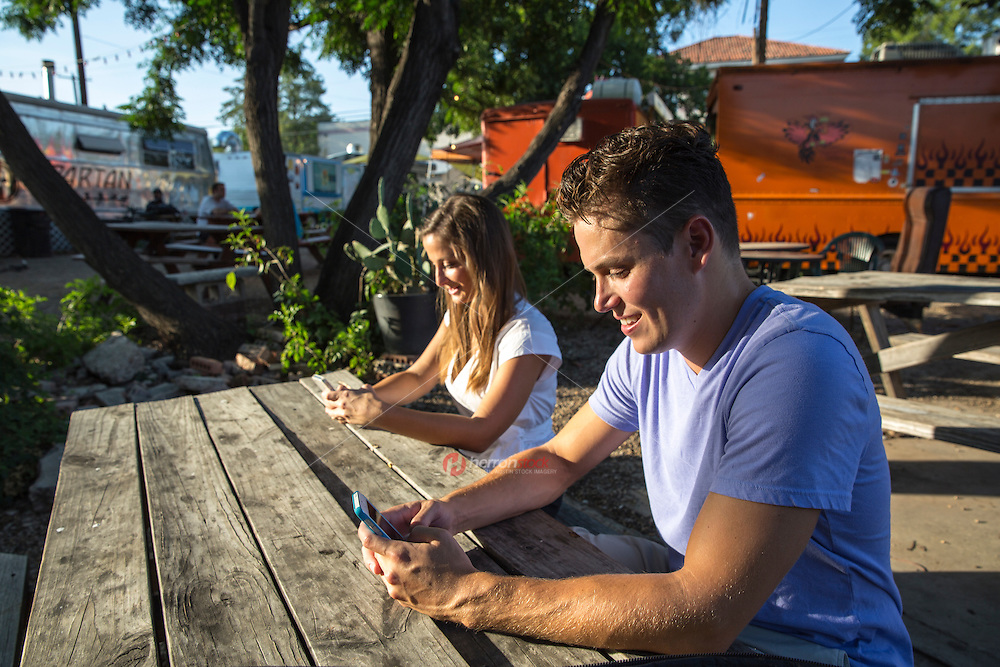 Young couple using mobile smart phones plans their evening from an East Austin Food Trailer Park in East Austin.