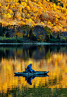 Man fishing from a kayak in Profile Lake, New Hampshire, USA.