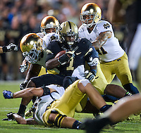 Boilermakers running back Akeem Hunt (1) is tackled by Notre Dame Fighting Irish linebacker Dan Fox (48)  and nose tackle Louis Nix (1) in the third quarter.