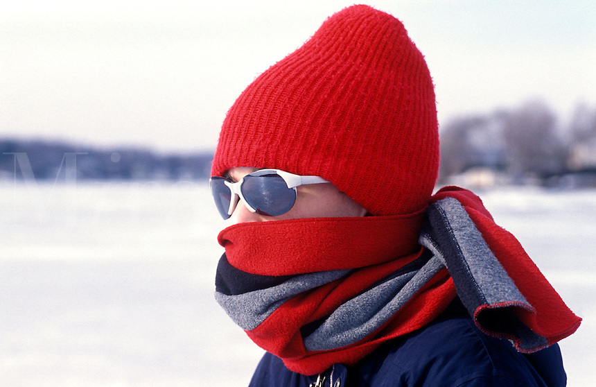 Young boy wrapped in winter clothes