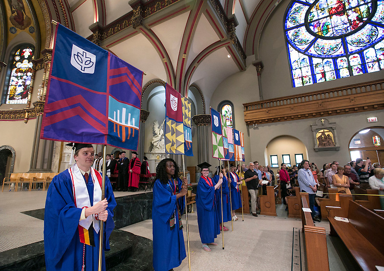 Graduates hold the college and school banners in the front of the St. Vincent de Paul Parish Church as students and their families join DePaul faculty and staff for the Baccalaureate Mass Friday, June 10, 2016. The event was part of the 118th commencement ceremonies for the Chicago university. (DePaul University/Jamie Moncrief)