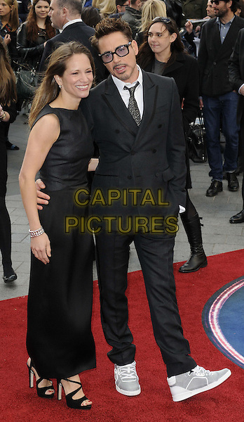 Susan Downey (nee Levin) & Robert Downey Jr.'Iron Man 3' UK film premiere, Odeon cinema, Leicester Square, London, England 18th April 2013..full length dress husband married wife glasses grey gray tinted blue lenses trainers black suit white shirt mouth open tie hand in pocket.CAP/CAN.©Can Nguyen/Capital Pictures.
