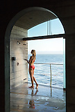 USA, California, Big Sur, Esalen, a woman takes a shower to rinse off at the Baths, the Pacifc Ocean in the distance, the Esalen Institute