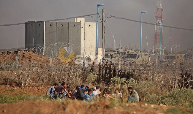 Palestinian protesters gather during clashes with Israeli security forces near the border fence between Israel and the Gaza Strip on October 9, 2015 east of Gaza City. Tension and protests rose after an Israeli man on 09 October stabbed four Palestinians in southern Israel, in what is being seen as a revenge attack, officials said. On 08 October several violent incidents happened, including stabbings which left eight Israelis injured, one Palestinian was killed in East Jerusalem and six in the Gaza Strip in clashes with the army while at least six were injured on the West Bank . Photo by Ashraf Amra