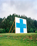 SWITZERLAND, Motiers, the symbol of the Swiss is displayed on the hillside above the town of Motiers, Jura Region