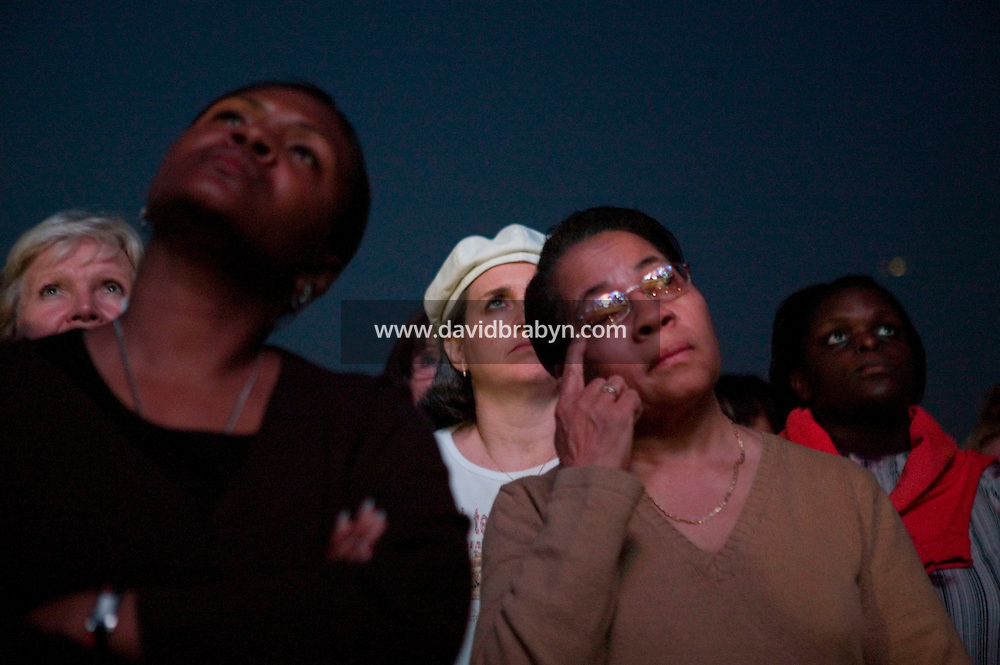 People follow 86 year-old evangelist Billy Graham's sermon on a giant screen on the first day of his three-day New York crusade at Flushing Meadows-Corona Park in Queens, NY, USA, Friday June 24 2005.