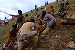 A young Rapa Nui girl slides down the 35-degree slopes of the volcano Maunga Pu'i for  Haka Pei - a competition where two banana tree stumps are tied together and used as a sled.  The competitor lies, back down on the sled and slide down a volcano mountainside. The competitors are judged by speed and by their ability to stay on the sled throughout the duration of the slide.