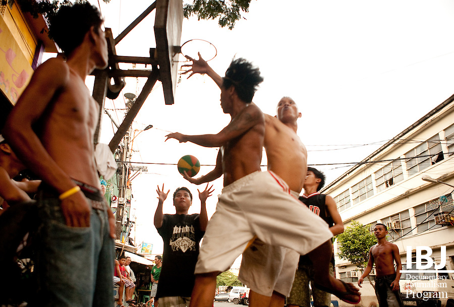 Basketball is very popular throughout the Philippines.  Here, a group of teenagers shut down a side street to play a pickup game.