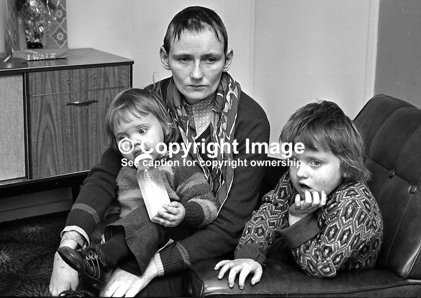 Mrs Roisin Fox, 20 years, Churchill Park, Portadown, Craigavon, N Ireland, who was beaten up and had her hair shorn when three masked men broke into her home. They claimed she was a police informer and gave her 48 hours to leave or be shot. She is pictured with her children Geraldine, 2 years, and Tony, 4 years. 197401170019a.<br />