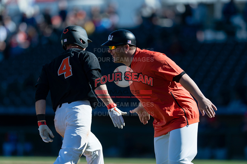 Oregon State Beavers third base coach Andy Jenkins congratulates Beau Philip (4) for hitting a three-run home run during a game against the Gonzaga Bulldogs on February 16, 2019 at Surprise Stadium in Surprise, Arizona. Oregon State defeated Gonzaga 9-3. (Zachary Lucy/Four Seam Images)