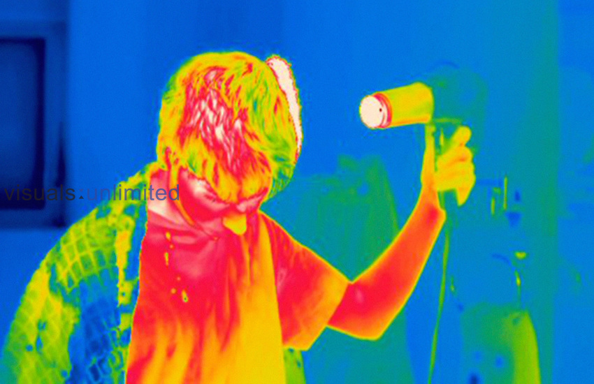 Thermogram of a male teenager blow drying his hair. The temperature scale runs from white (warmest) through red, yellow, green and cyan, blue and black (coldest).