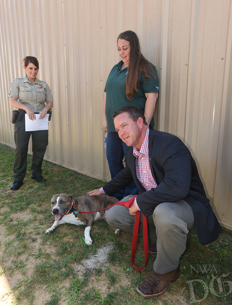 NWA Democrat-Gazette/FLIP PUTTHOFF <br />Shawn Holloway, Benton County Sheriff, on Tuesday July 11 2017 pets Cruise, a New Leash on Life canine at the Benton County Jail. With Holloway are Sgt. Shannon Jenkins (left) with the sheriff's office and Tiffany Thompson with Pet Supply Plus.