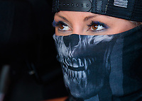 Jun 7, 2019; Topeka, KS, USA; NHRA top fuel driver Leah Pritchett wears a skeleton print face mask as she warms up her dragster during qualifying for the Heartland Nationals at Heartland Motorsports Park. Mandatory Credit: Mark J. Rebilas-USA TODAY Sports