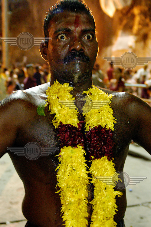 An ethnic Tamil man reaches the ecstatic climax of his pilgrimage to the Batu Caves, as part of the annual Thaipusam festival of penance and thanksgiving.  A skewer has been removed from his tongue and he will pass out after reaching a moment of ritual release.  The Tamil Hindu festival commemorates the birth of Hindu Lord Murugan and his triumph over evil. Pilgrims engage in various acts of devotion such as carrying burdens, flagellation and body piercing as they take part in a 15-kilometre procession to the Batu Caves. ..