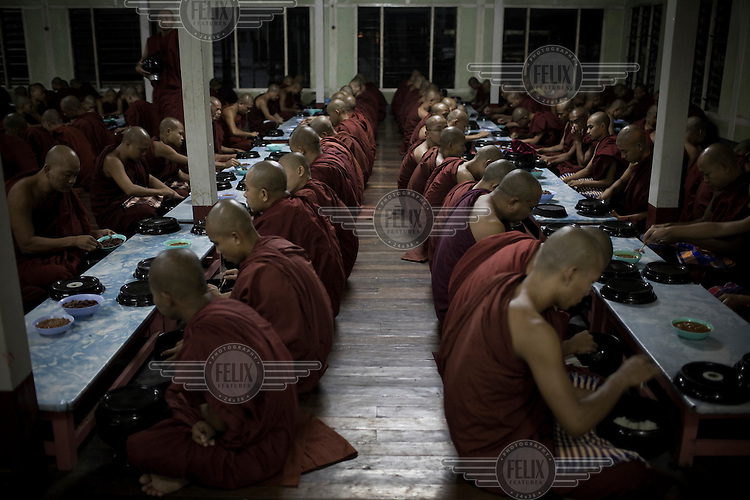 Monks pray before eating their breakfast, at a monastery on the outskirts of Mandalay, where over 2,300 monks study and live.