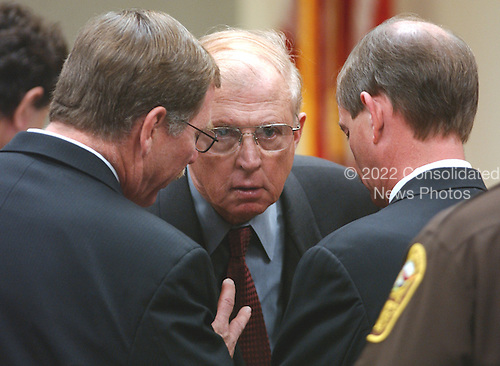 Prince William County (Virginia) Commonwealth Attorney Paul S. Ebert, center, talks with his team Richard Conway, left, and James Willett, right, during the trial of sniper suspect John Allen Muhammad at the Virginia Beach Circuit Court in Virginia Beach, Virginia on November 13, 2003. <br /> Credit: Steve Earley - Pool via CNP