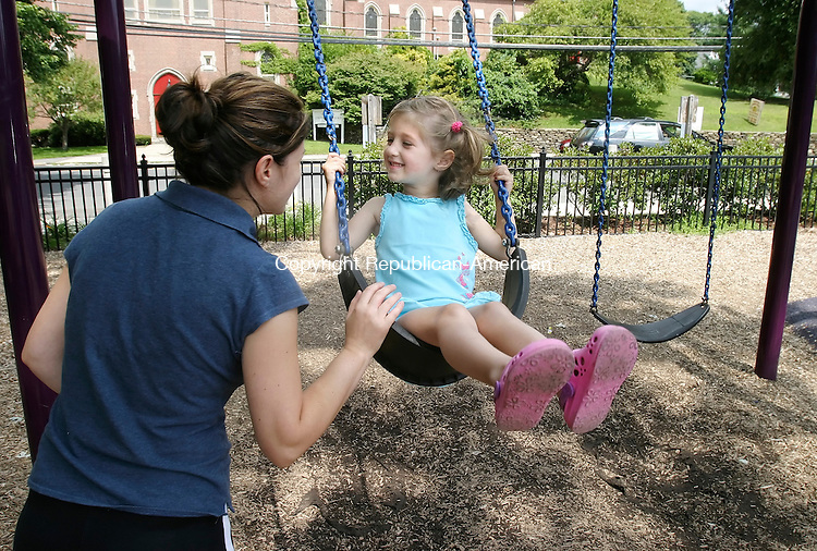 WATERBURY, CT, 08/19/08- 081908BZ01- Dea Raidhi, 3, smiles at her mother Ariola Raidhi, while playing on the swings at Schofield Park in Waterbury Tuesday.<br /> Jamison C. Bazinet Republican-American
