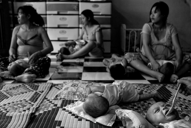 Expecting mothers feed newborns at a halfway home for pregnant teenagers.