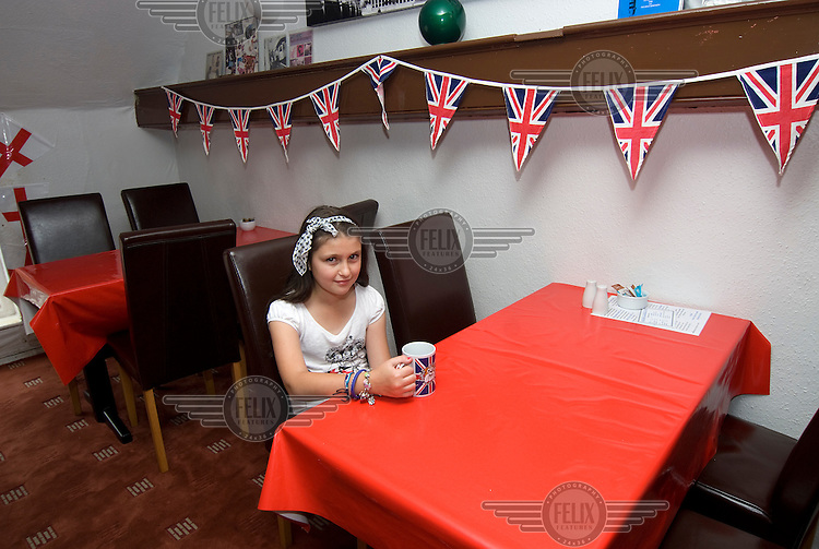 A young girl sits alone with a cup of tea at a cafe in Lincoln. Decorative bunting is hung around the room all with the design of the British flag.