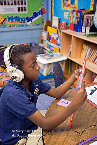 One African American seven year old boy wears earphones and listens to story while holding written page in classroom in New Orleans,Louisiana.
