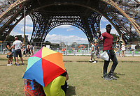 PARIS,FRANCE - AUGUST 8: Tourists enjoying the view and a man sells souvenirs at the Champ-de-Mars next the Eiffel Tower (Gustave Eiffel1887-1889) with men working in the construction of a bulletproof glass barrier along of the Eiffel Tower is part of a broader €35 million ($41 million) security project in Paris,France.(Photo by Paulo Amorim)