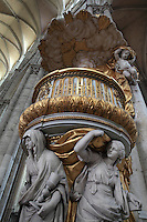 The pulpit, carved in wood then painted and gilded in 1773, designed by Pierre-Joseph Christophle, 1715-1782, with statues representing Faith, Hope and Charity supporting the pulpit, drapery being lifted by angels, and a cloud canopy, on the north side of the nave in the Basilique Cathedrale Notre-Dame d'Amiens or Cathedral Basilica of Our Lady of Amiens, built 1220-70 in Gothic style, Amiens, Picardy, France. Amiens Cathedral was listed as a UNESCO World Heritage Site in 1981. Picture by Manuel Cohen