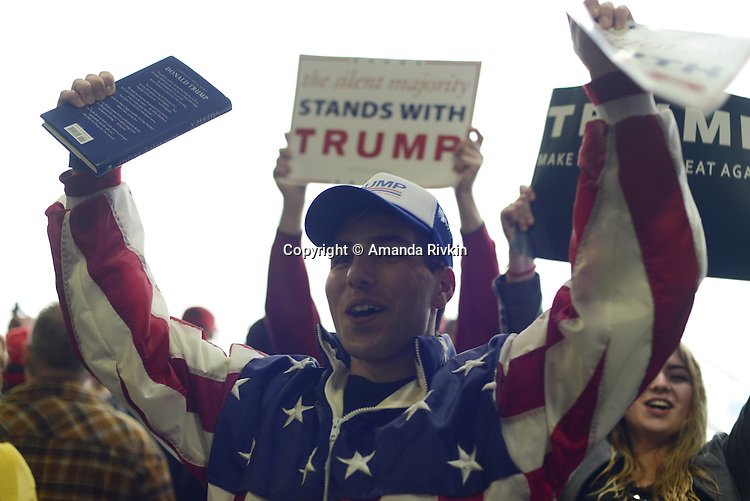 "Trump supporters get rallied up to chants of ""Build The Wall"" inside the Synergy Flight Center to hear Republican front runner Donald Trump speak in Bloomington, Illinois on March 13, 2016."