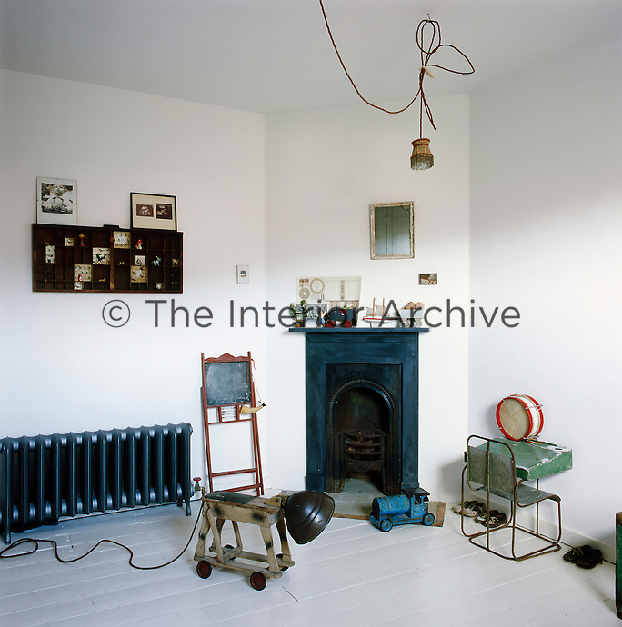 A child's bedroom with a Victorian fireplace in one corner. The white room has painted floorboards and a retro style radiator. Vintage toys are dotted around the room and a small metal desk and chair stands against one wall.