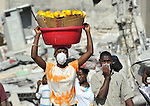 Her face masked because of the smell of decomposing bodies trapped in the rubble, a woman walks in Port-au-Prince, Haiti, much of which was devastated in a January 12 earthquake.