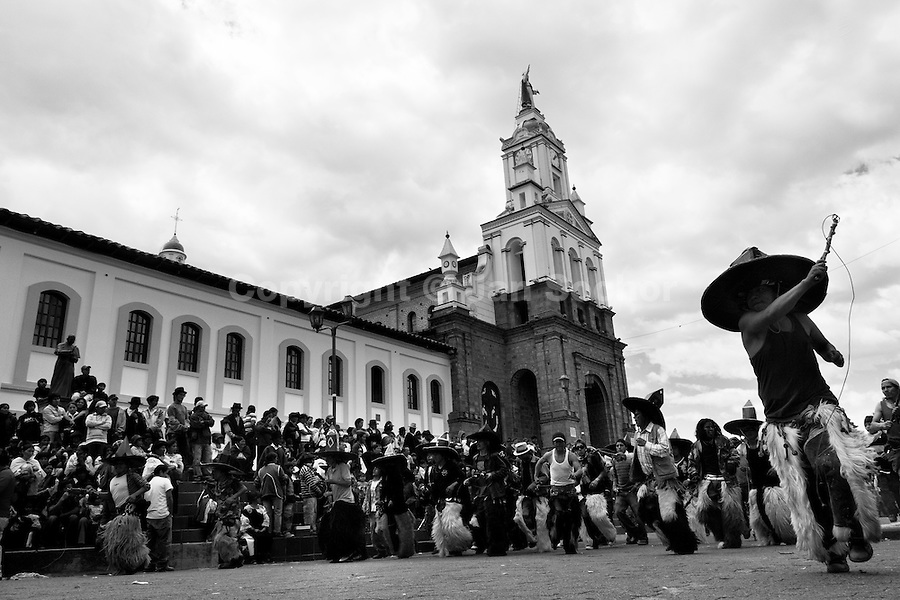 Indians, wearing goatskin chaps, dance furiously during the Inti Raymi (San Juan) festivities in front of the church in Cotacachi, Ecuador, 24 June 2010. 'La toma de la Plaza' (Taking of the square) is an ancient ritual kept by Andean indigenous communities. From the early morning of the feast day, various groups of San Juan dancers from remote mountain villages dance in a slow trot towards the main square of Cotacachi. Reaching the plaza, Indians start to dance around. They pound in synchronized dance rhythm, shout loudly, whistle and wave whips, showing the strength and aggression. Dancers from either the upper communities (El Topo) or the lower communities (La Calera), joined in respective coalitions, seek to conquer and dominate the square and do not let their rivals enter. If not moderated by the police in time, the high tension between groups always ends up in violent clashes.