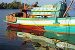 Colourful reflections of traditional Cham fishing boat stern reflected in ripples on the Sanke river at dawn, Kampot, Cambodia.