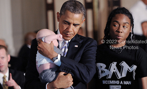 United States President Barack Obama holds a baby at a Father's Day luncheon to celebrate the importance of strong families and mentorship in the State Dining Room of the White House June 14 , 2013 in Washington, D.C. .Fathers and their children as well as students and leaders from the Becoming a Man (BAM) program at Hyde Park Academy in Chicago attend the event.<br /> Credit: Olivier Douliery / Pool via CNP