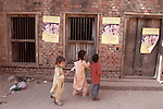 VARANASSI, UTTAR PRADESH, INDIA, FEBRUARY 22, 2004 : Children walk past Polio Immunization day posters during the National Immunization Days in Varanassi, on February 22, 2004. India confirmed 1600 polio cases in 2002 , most of them in the states of Bihar and Uttar Pradesh. India is trying to eliminate polio transmition by 2005 with agressive vaccination campaigns targetting at risk areas. (Photo Jean-Marc Giboux)